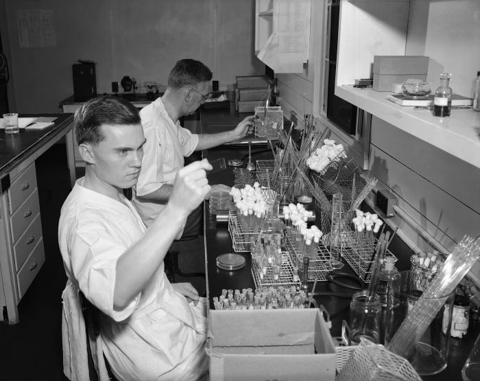 This historic image, photographed sometime between 1948 and 1963, featured two men seated in their Enteric Bacteriology Unit laboratory perf