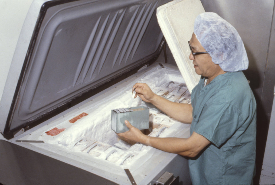 This laboratorian is retrieving specimens from a freezer during a laboratory training session.