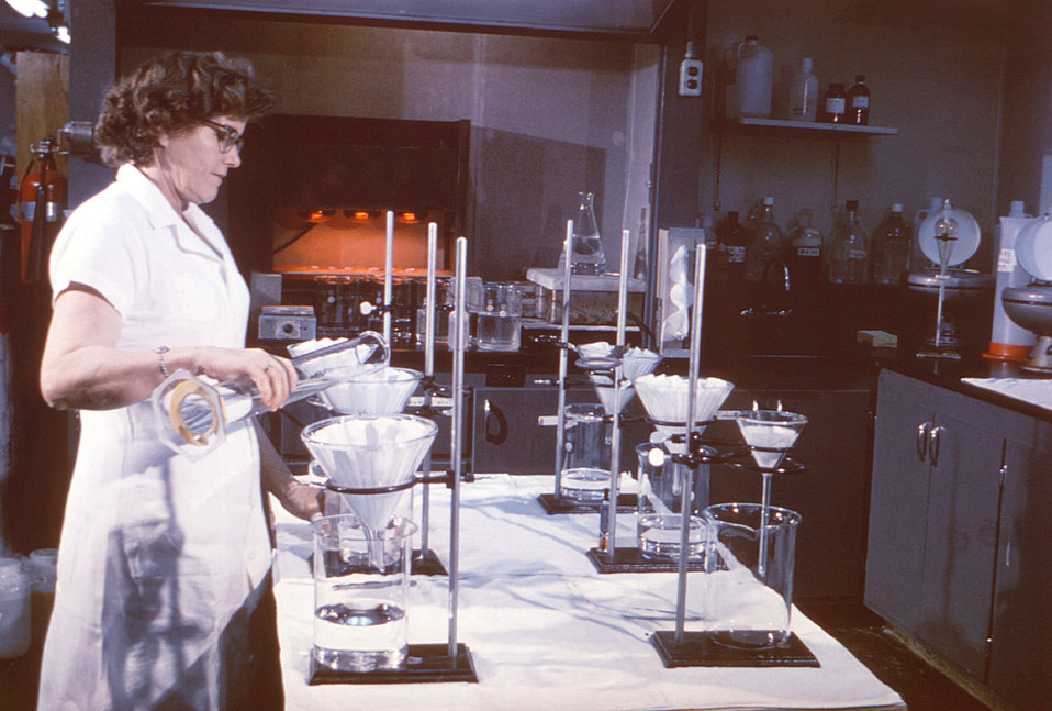 This historic 1963 image depicted a laboratory technician as she was in the process of filtering water samples prior to carrying out a radio
