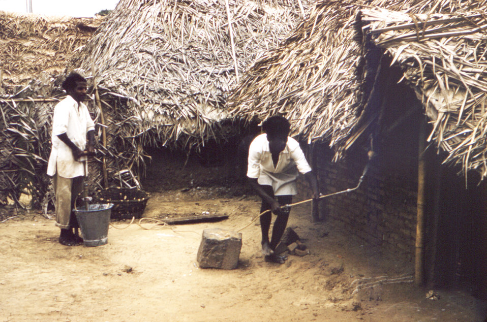 This historic 1961 image depicted two men in a village in India, as they were in the process of spraying the insecticide DDT (dichlorodiphen