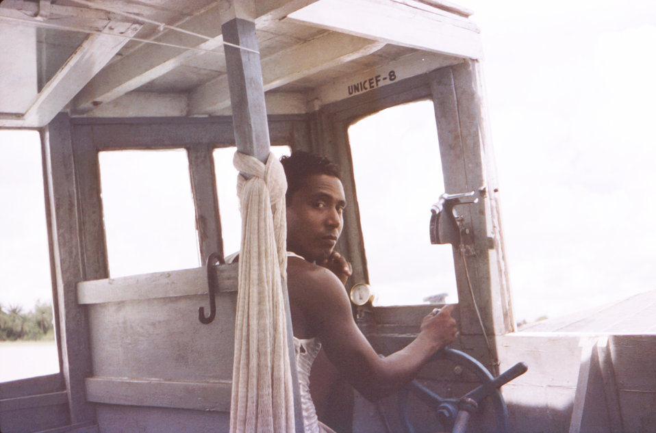 This October, 1975 photograph depicted boat Captain, and driver, Robin Gomes, while at the helm of a 'UNICEF 8' boat on a Patuakhali Distric