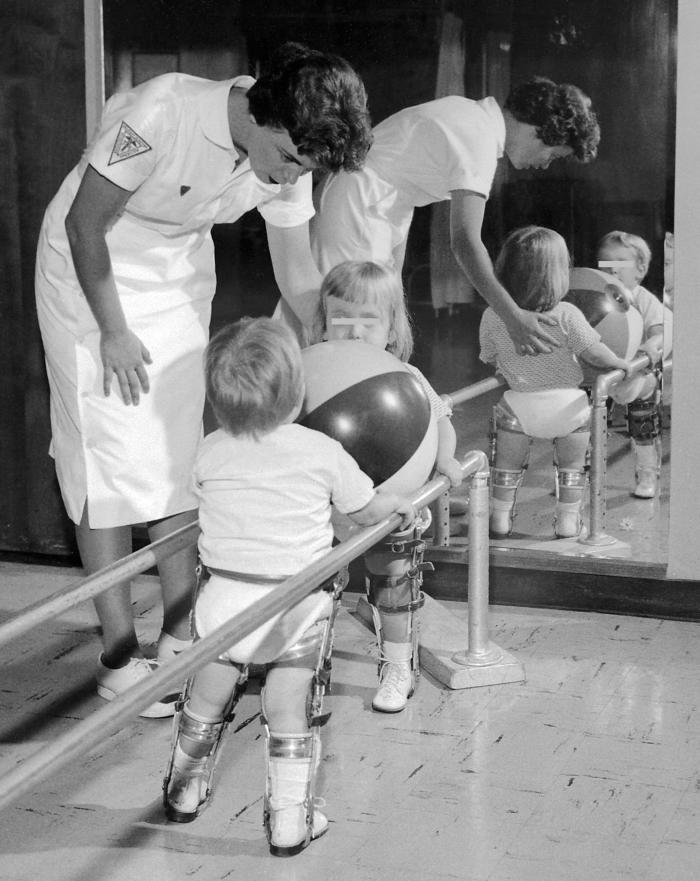 This physical therapist is assisting two polio-stricken children holding on to a rail while they exercise their lower limbs.
