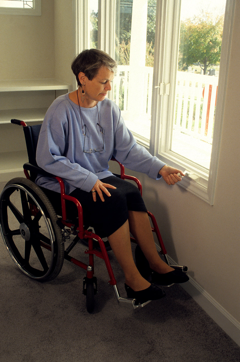 In this 1995 image, a woman seated in a wheelchair was operating a manual hand crank on a casement window.  Because the crank was located on