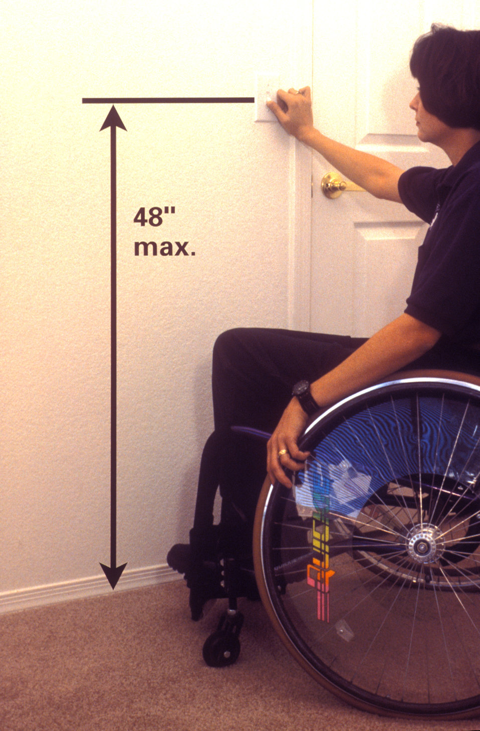 Photographed in 1997, this image depicted a wheelchair-seated woman as she was interacting with a wall-mounted light switch. Crucial to the
