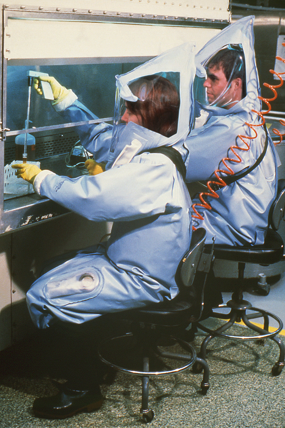 This image depicts two Centers for Disease Control laboratorians, Luanne Elliot and Dave Auperin, as they were working under a flow hood ins
