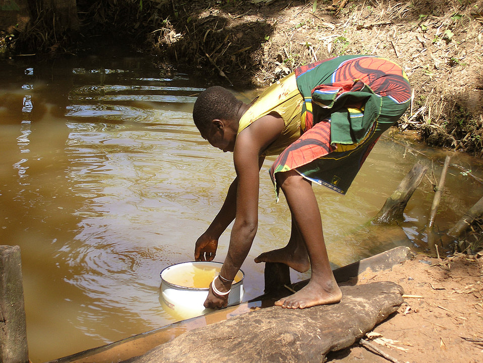 This young girl was collecting water from a sacred pond in Ogi, Nigeria, but she won't get Guinea worm because the water had been treated, a