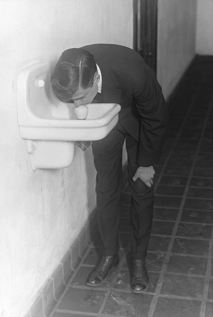This historic 1917 photograph showed a man drinking from an unsatisfactorily designed drinking water fountain on the campus of a Minnesota u