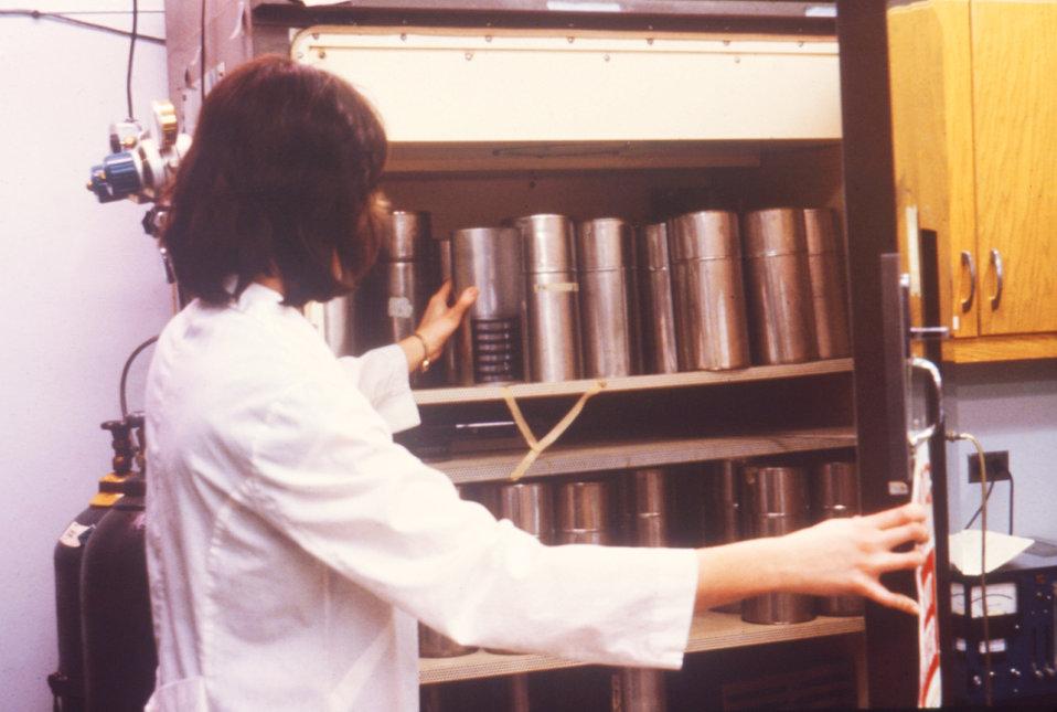 Photograph of microbiologist placing cultures of Legionella pneumophila in CO2 incubator.