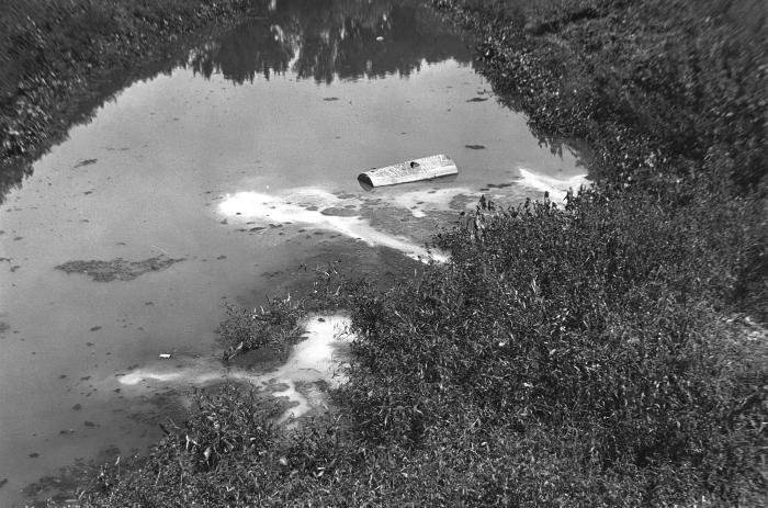 This historic 1934 photograph revealed the discharge of industrial wastes from a sewer outlet into Straight River at Owatonna, Minnesota. Th