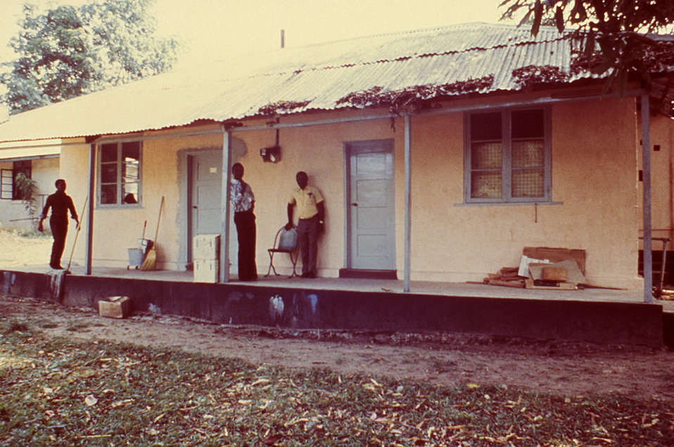 This 1977 image depicts the front entrance of the Kenema Laboratory located in Sierra Leone with some of the staff members.