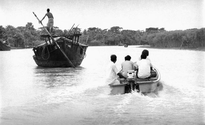 This image depicted the juxtaposition of two modes of river transport. On the left, a large river boat was traveling using a steering rudder