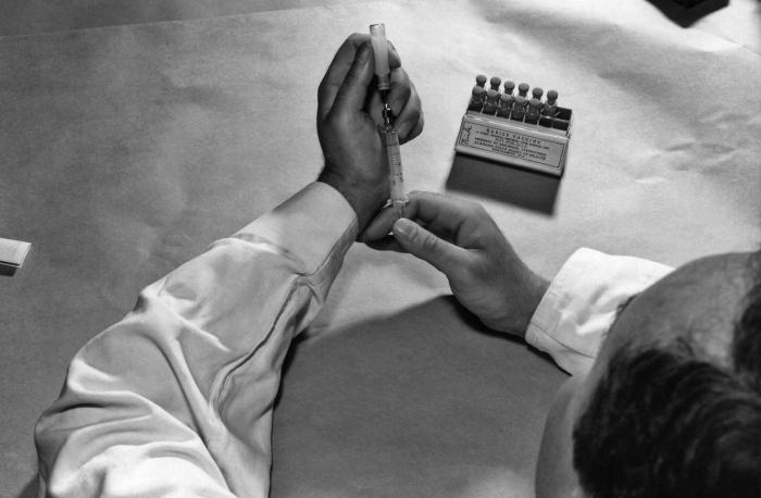 This photograph shows a CDC laboratorian as he was filling a syringe with rabies vaccine that had been obtained from the Alabama State Board