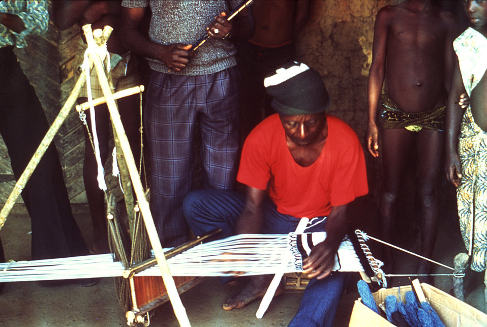 This 1977 image depicts a Motehun, Sierra Leone weaver practicing his craft at a loom as fellow villagers watch.