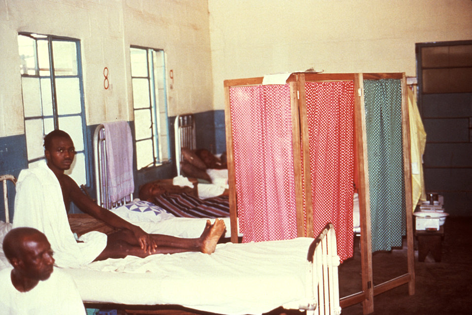 This 1977 image depicts the 'barrier nursing' practiced on the male patient Lassa fever ward in Segbwema, Sierra Leone.
