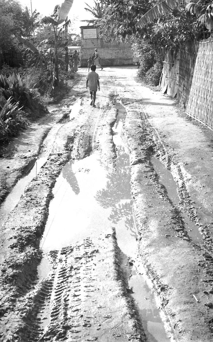 This image depicted a muddy road in a typical Bangladesh town, which was traversed by numerous tire tracks, including those from the smallpo