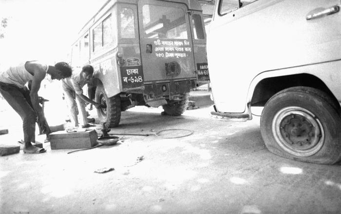 These two mechanics were photographed while they were repairing the left rear tire on a smallpox eradication team Mahendra jeep. This image
