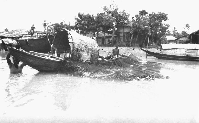 This image depicted a Bangladesh fishing boat with two occupants. One young man was still onboard the craft, and had cast a fishing net from