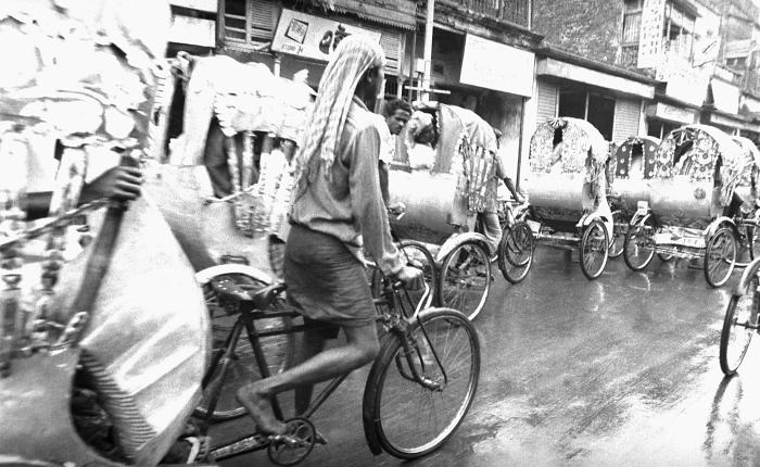 This Bangladesh town street scene depicted a roadway crowded with rickshaws transporting passengers throughout the town. This photograph pro