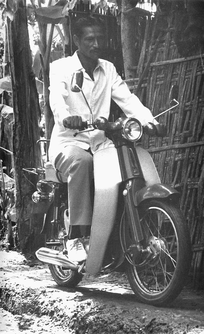 This photograph depicted a smallpox eradication team member riding upon a motor scooter as he rode from town to town in search of any smallp