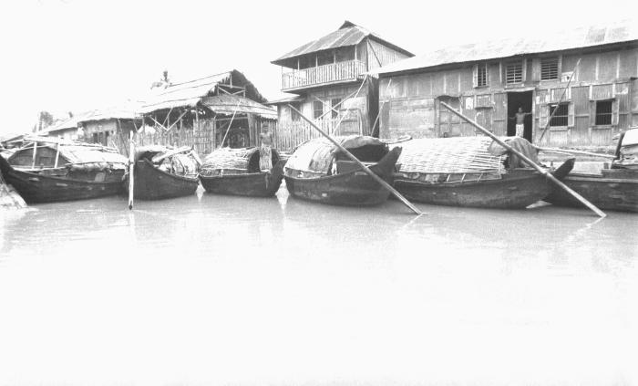 This image depicted a number Bangladesh country boats that are docked alongside processing establishments. This image was part of a series p
