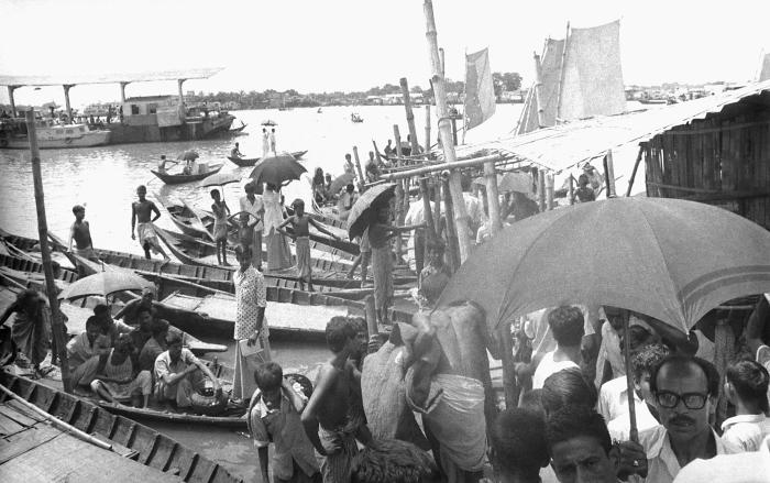 This photograph depicted a crowded town boat terminal where passengers were disembarking and boarding water craft, as they traveled from tow