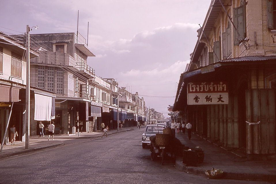 This is a 1964 photograph depicting store fronts in the Old City section of Bangkok, Thailand.