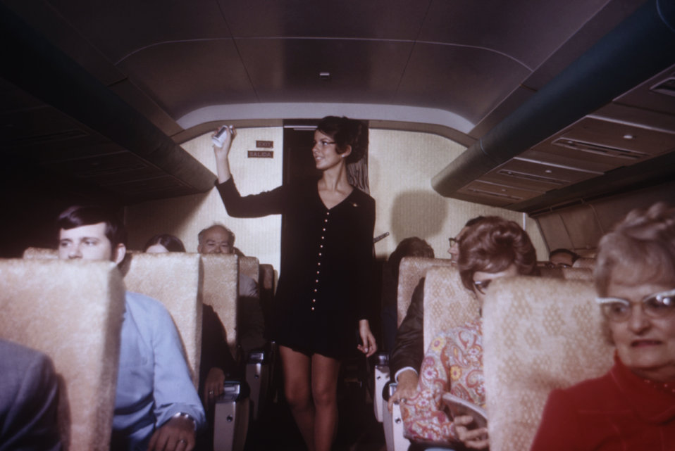 This is a 1971 photograph showing an airline employee spraying inside an aircraft with an aerosol pesticides spray.