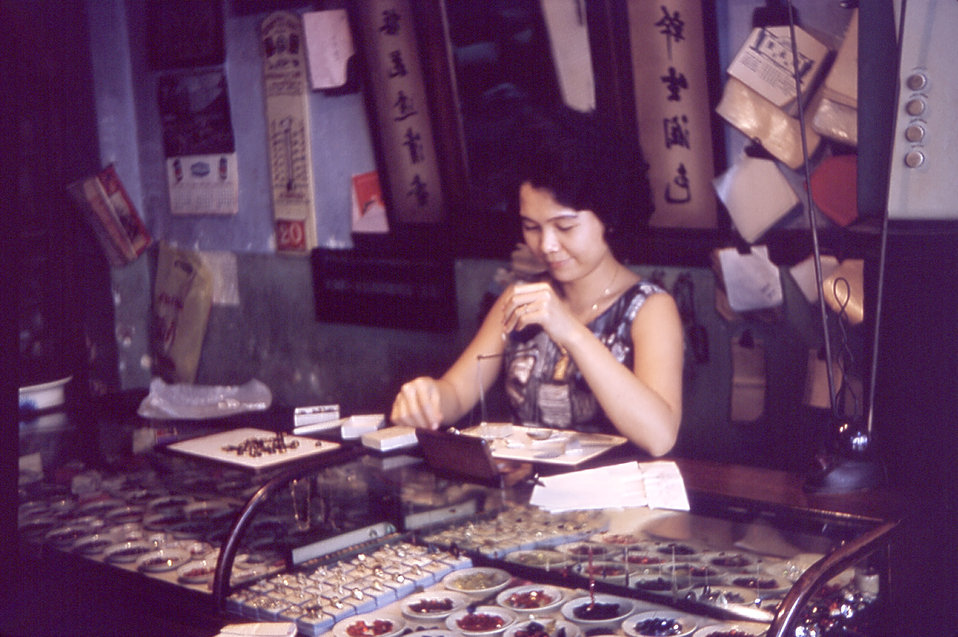 This 1964 image depicts an attendant assisting a customer in the purchase of star sapphires in Bangkok, Thailand.