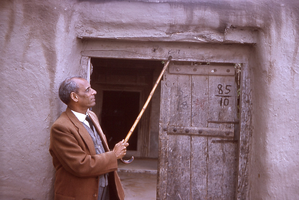 This is a photograph of a local health official named Nurahmed pointing to a house number in a Gujarat, India village.