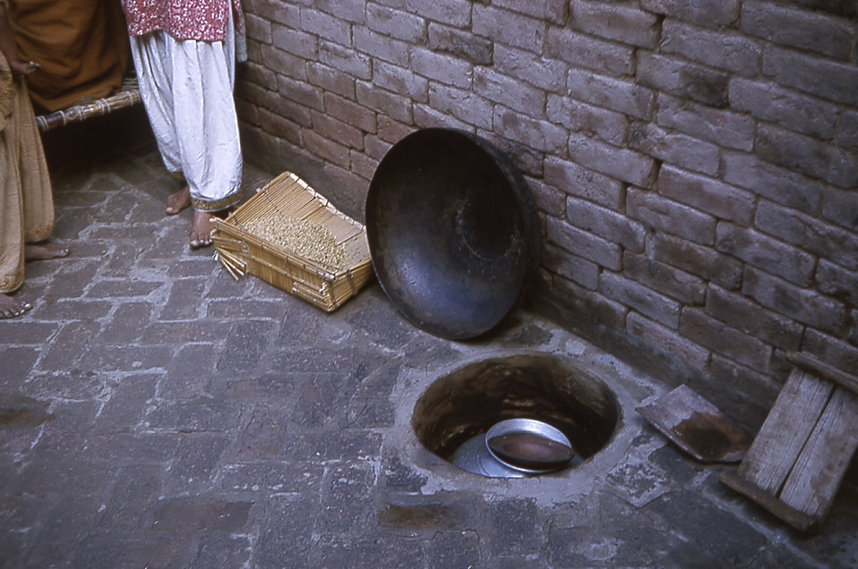 The warming of milk in a below-ground oven is typical of village life in the state of Gujarat, India.