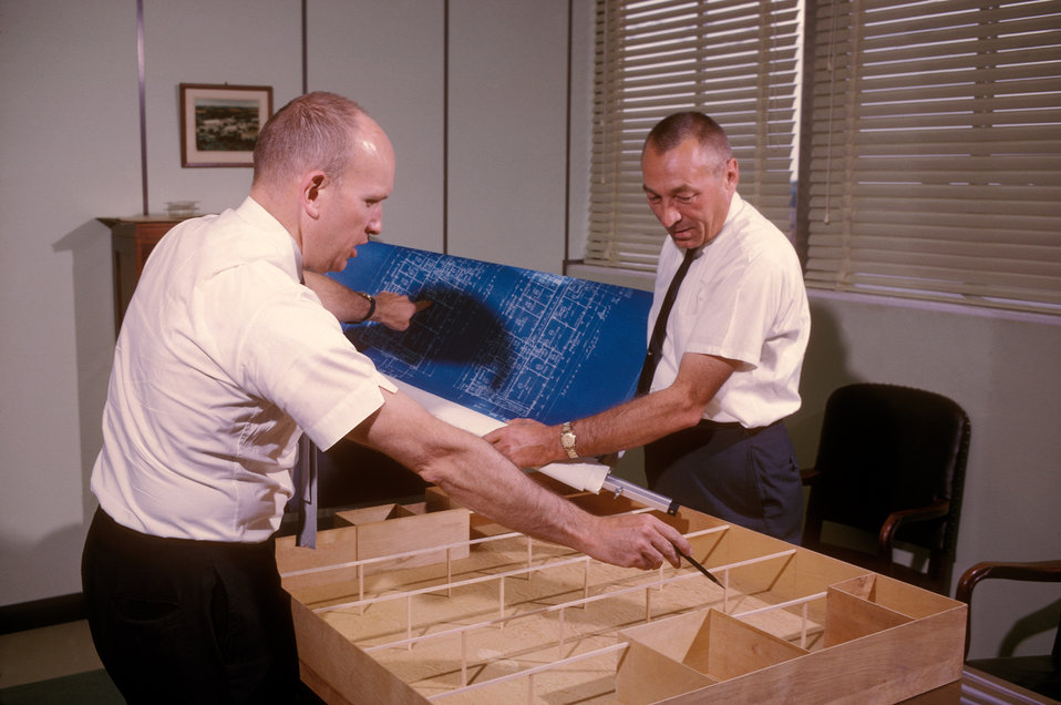 This 1965 photograph showed James G. Paine (left), and R. Meuleners going over the blueprint and model of a new CDC facility which was being