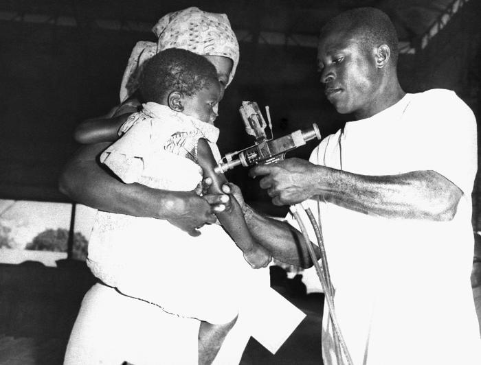 This 1967 photograph depicted a Togolese woman having her child vaccinated against smallpox. It was taken just prior to the kick-off of the