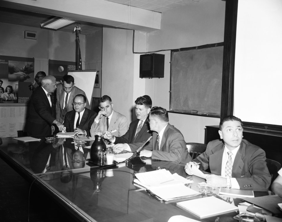 This 1956 photograph depicts a number of CDC officials during a bid opening meeting for the construction of new CDC facilities.