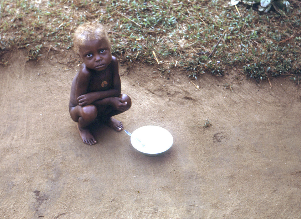 This late 1960s photograph shows a child after finishing a meal provided by a CDC relief operation during the Nigerian-Biafran war. The chil