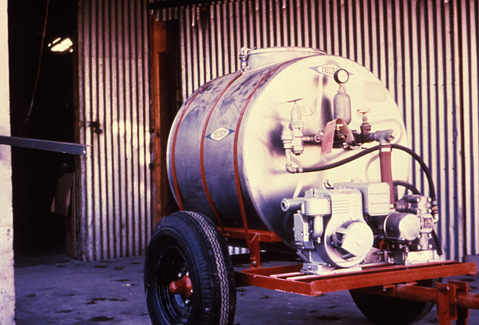 This 1981 photograph depicts an orchard sprayer, used to deliver a high volume of mist to agricultural crops, which includes insecticides, f