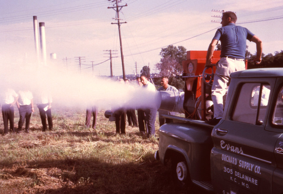 This 1981 photograph depicts field technicians examining a Buffalo Turbine Sprayer/Duster as it delivers a cloud of insecticide from its noz
