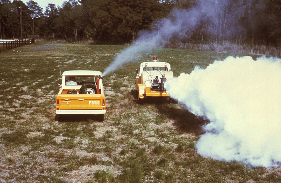This 1981 image depicts a demonstration of two fog generators, an ultra-low volume (ULV) generator (Lt), and a thermal fog generator (Rt).