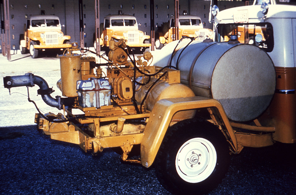 This 1981 photograph depicts an older model Todd insecticidal fog applicator (TIFA) thermal fogger, used to deliver a high volume of fog to