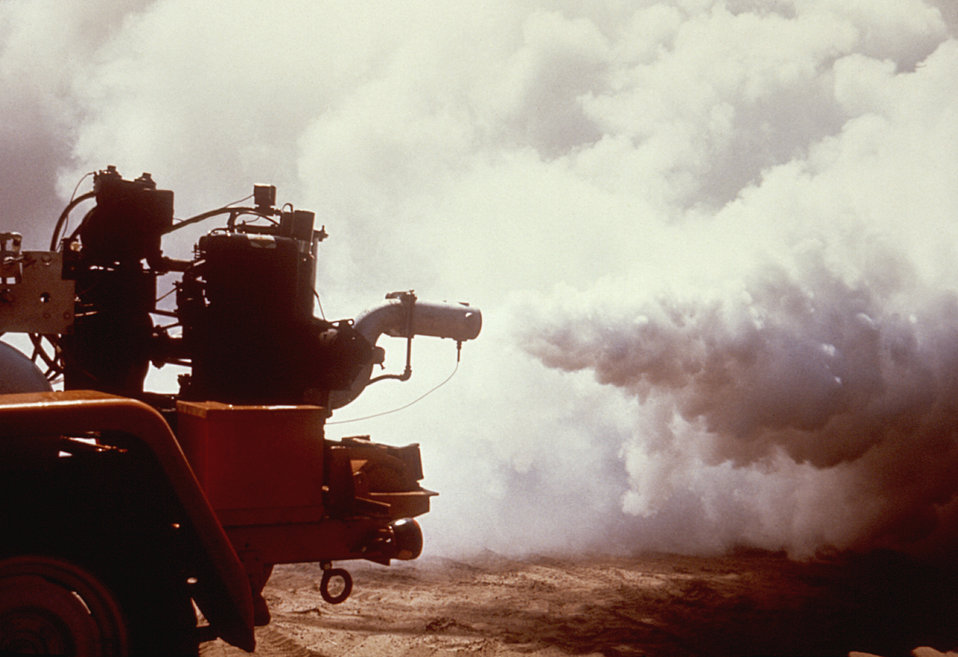 This 1981 photograph depicts an operating older model Todd insecticidal fog applicator (TIFA) thermal fogger, being demonstrated as it deliv