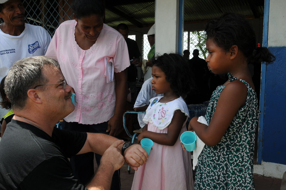 This 2008 photograph depicts U.S. Public Health Service (USPHS), Cmdr. Dale Bates talking to young female patients and their parents, as he
