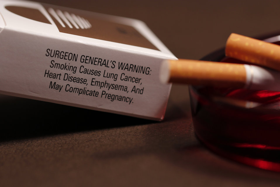 In its background, this image depicts an opened pack of cigarettes with its side-panel health warning to would-be smokers stating some of th
