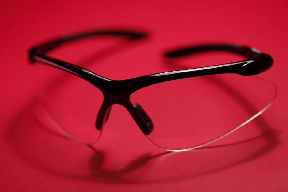 Set upon a bright red background, this image depicts a pair of protective laboratory eyewear consisting of clear colorless plastic lenses se