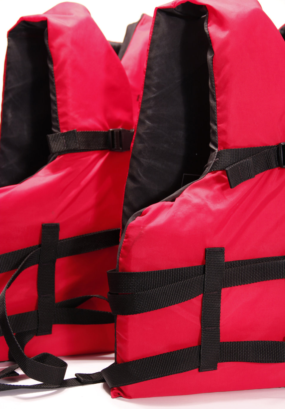 This photograph depicts two life vests, also known as life jackets, that displayed a bright red exterior, and were lined with a black interi