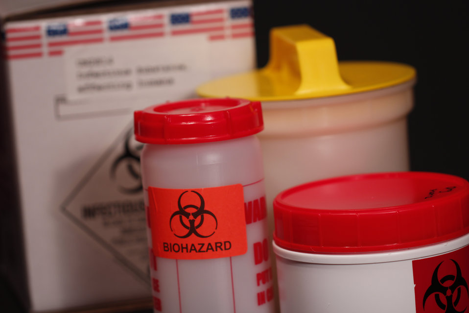 This photograph demonstrates three cylindrical-shaped containers, which are used in the shipment of biohazardous materials. In the backgroun