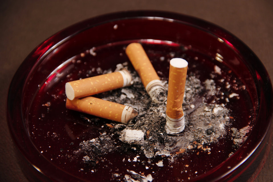 This image depicts a ruby-colored glass ashtray, which contained four used cigarette butts along with their ashes.