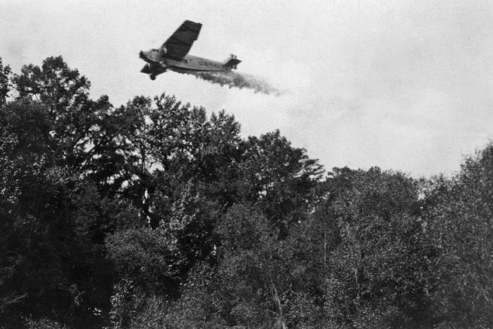 In an attempt at vector control, this 1930s photograph showed a Ford Trimotor aircraft as it was spraying insecticide, in order to help elim