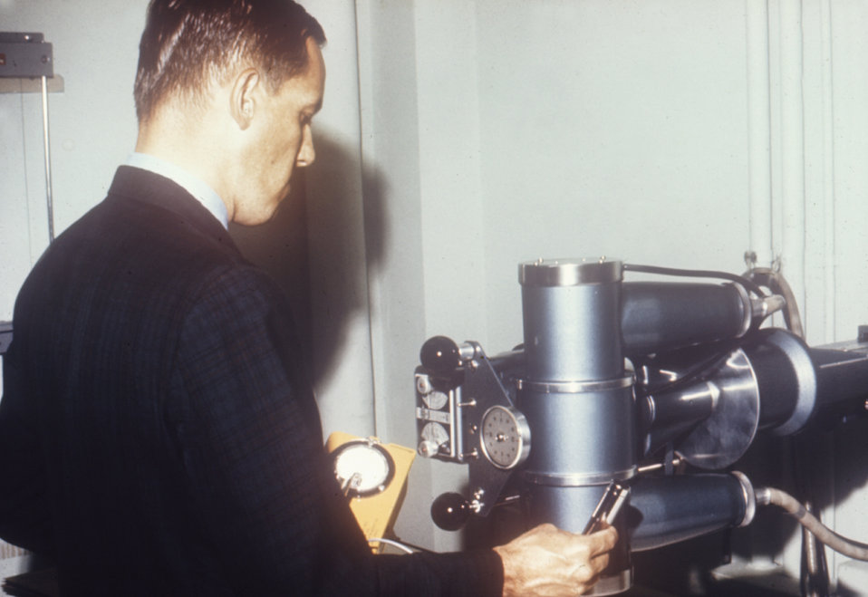 This 1970 photograph shows a radiologic health sanitarian with a Geiger counter surveying an x-ray machine in a clinic.