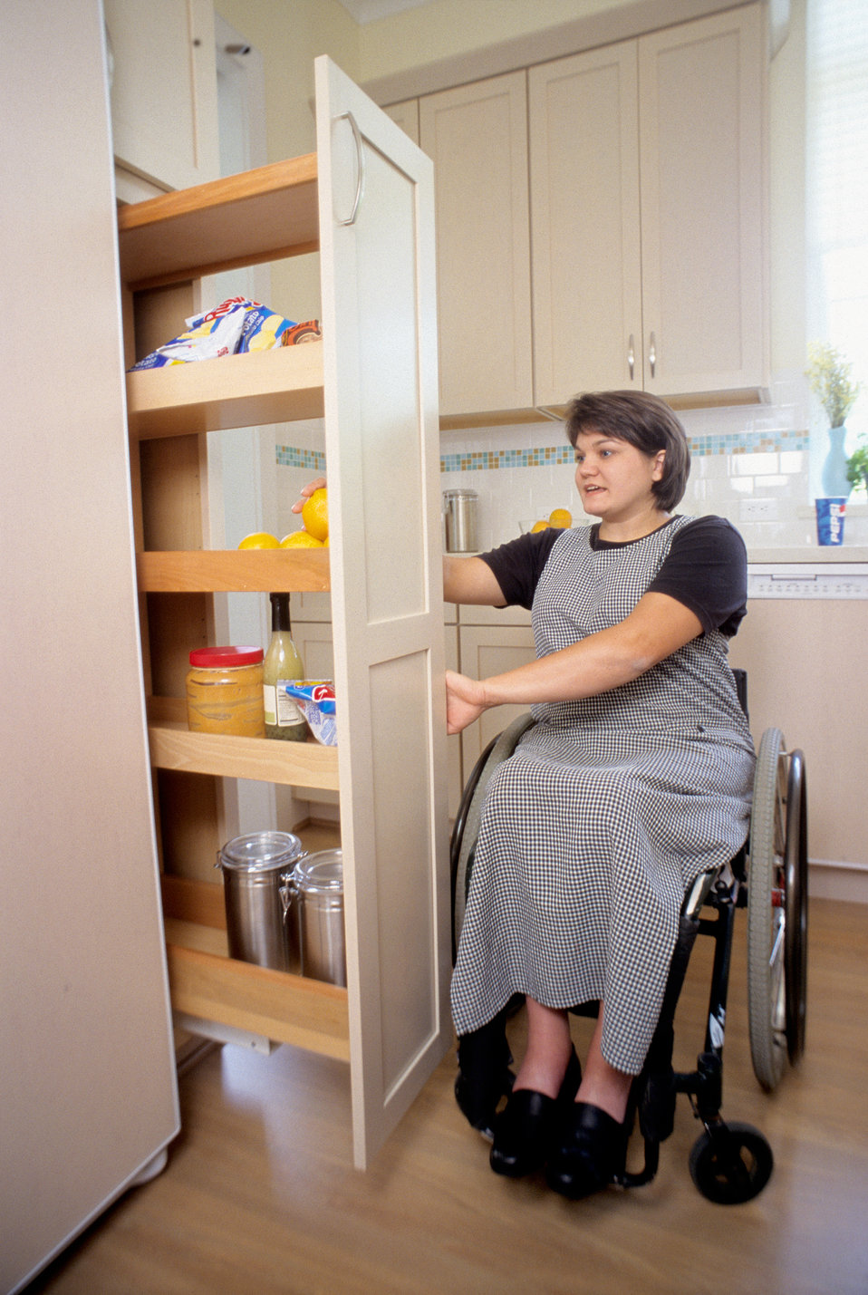 While seated in her wheelchair, in this 2000 image, an adult woman was shown as he was navigating the contents of a kitchen situated 'pull-o