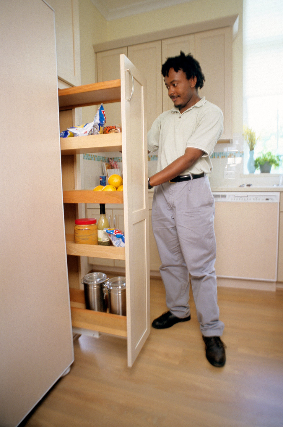 In this 2000 image, an adult man was shown as he was navigating the contents of a kitchen-situated 'pull-out' pantry, in order to illustrate