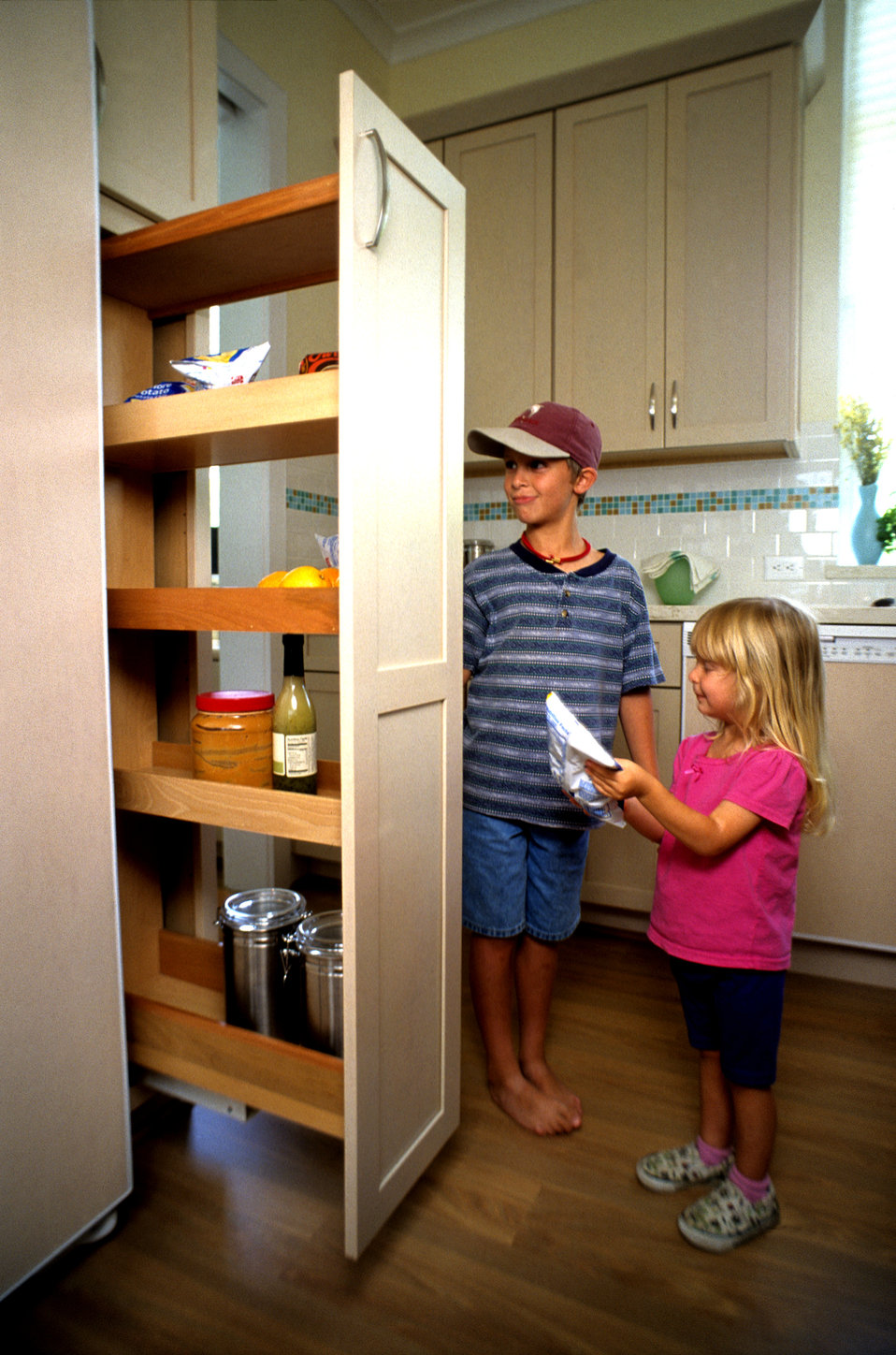 This sister and brother, were photographed in this 2000 image in order to illustrate how the installation of a 'pull-out' pantry inside this